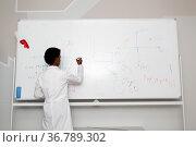 African American woman math teacher writing on blackboard with marker. Стоковое фото, фотограф Zoonar.com/Max / easy Fotostock / Фотобанк Лори