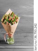 Bouquet of pink tulips in a package of kraft paper, on gray wodden... Стоковое фото, фотограф Zoonar.com/Konstantin Malkov / easy Fotostock / Фотобанк Лори