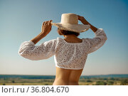 Erotic woman in hat poses in field, back view. Стоковое фото, фотограф Tryapitsyn Sergiy / Фотобанк Лори