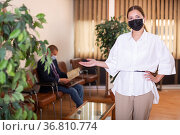 Portrait of a young confident girl in a protective mask standing in the lobby. Стоковое фото, фотограф Яков Филимонов / Фотобанк Лори