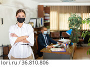Portrait of a young female employee wearing a protective mask standing in a office. Стоковое фото, фотограф Яков Филимонов / Фотобанк Лори