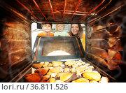 Mother with children open an oven door for cookies. Стоковое фото, фотограф Сергей Новиков / Фотобанк Лори