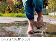 Woman wearing rain rubber boots walking running and jumping into puddle... Стоковое фото, фотограф Zoonar.com/Max 4e / easy Fotostock / Фотобанк Лори