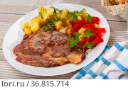 Appetizing beef entrecote with french fries and stewed bell peppers at plate. Стоковое фото, фотограф Яков Филимонов / Фотобанк Лори