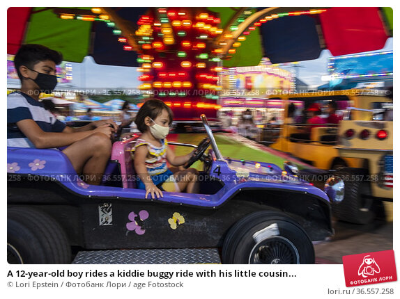 A 12-year-old boy rides a kiddie buggy ride with his little cousin... Редакционное фото, фотограф Lori Epstein / age Fotostock / Фотобанк Лори