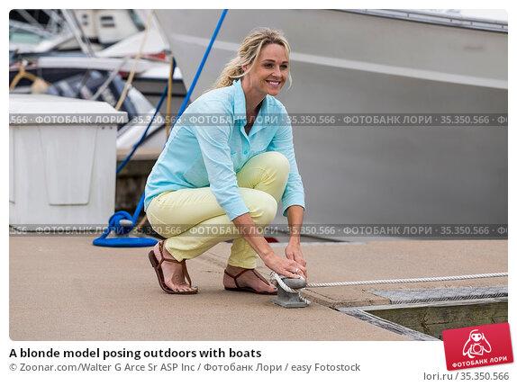 A blonde model posing outdoors with boats. Стоковое фото, фотограф Zoonar.com/Walter G Arce Sr ASP Inc / easy Fotostock / Фотобанк Лори