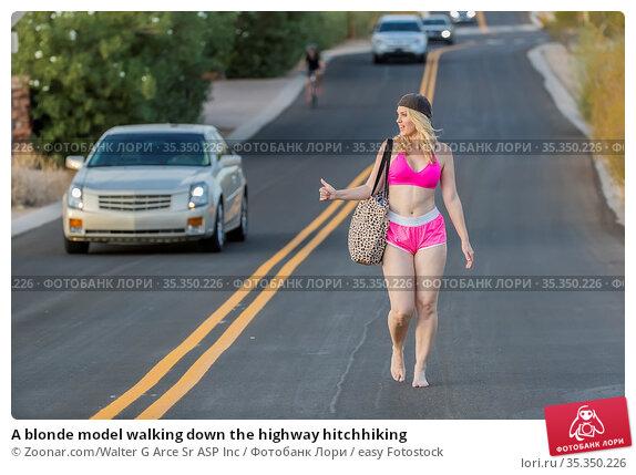 A blonde model walking down the highway hitchhiking. Стоковое фото, фотограф Zoonar.com/Walter G Arce Sr ASP Inc / easy Fotostock / Фотобанк Лори