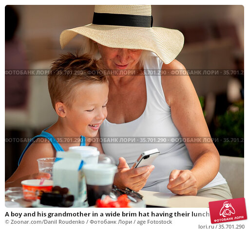 A boy and his grandmother in a wide brim hat having their lunch outdoor... Стоковое фото, фотограф Zoonar.com/Danil Roudenko / age Fotostock / Фотобанк Лори