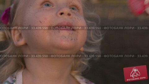 Купить «A closeup of a girls face blowing soap bubbles», видеоролик № 33439550, снято 27 марта 2020 г. (c) Данил Руденко / Фотобанк Лори
