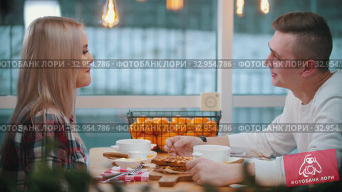 A couple in cafe having a lunch and talking to each other. Стоковое видео, видеограф Константин Шишкин / Фотобанк Лори