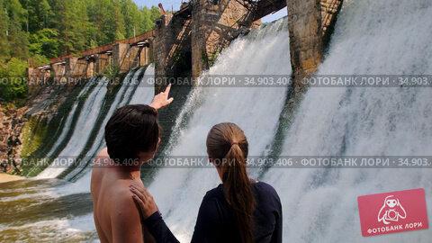 A couple on vacation in the forest - man and woman watching the waterfall dam. Стоковое видео, видеограф Константин Шишкин / Фотобанк Лори