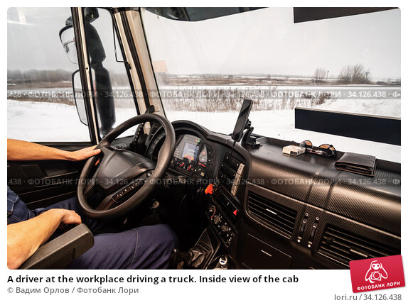 Купить «A driver at the workplace driving a truck. Inside view of the cab», фото № 34126438, снято 17 декабря 2019 г. (c) Вадим Орлов / Фотобанк Лори
