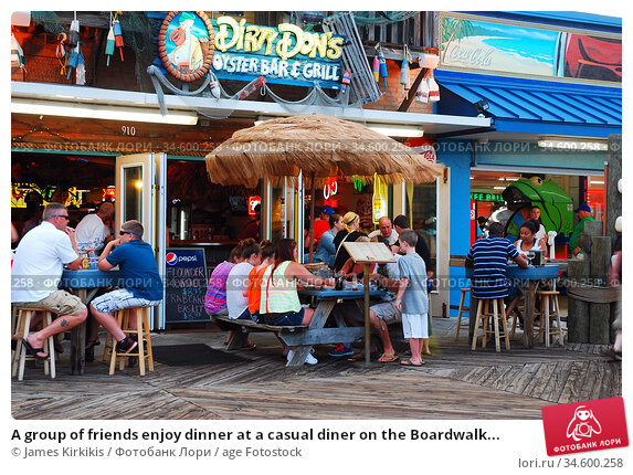 A group of friends enjoy dinner at a casual diner on the Boardwalk... (2013 год). Редакционное фото, фотограф James Kirkikis / age Fotostock / Фотобанк Лори