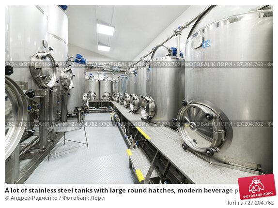 Купить «A lot of stainless steel tanks with large round hatches, modern beverage production.», фото № 27204762, снято 5 июля 2017 г. (c) Андрей Радченко / Фотобанк Лори