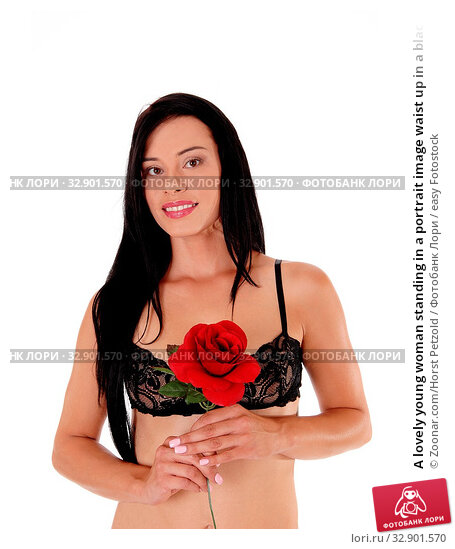 A lovely young woman standing in a portrait image waist up in a black bra, looking into the camera, with red rose, isolated for white background. Стоковое фото, фотограф Zoonar.com/Horst Petzold / easy Fotostock / Фотобанк Лори