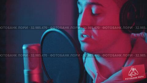 Купить «A man in headphones rapping through the pop-filter in the microphone», видеоролик № 32985470, снято 9 апреля 2020 г. (c) Константин Шишкин / Фотобанк Лори