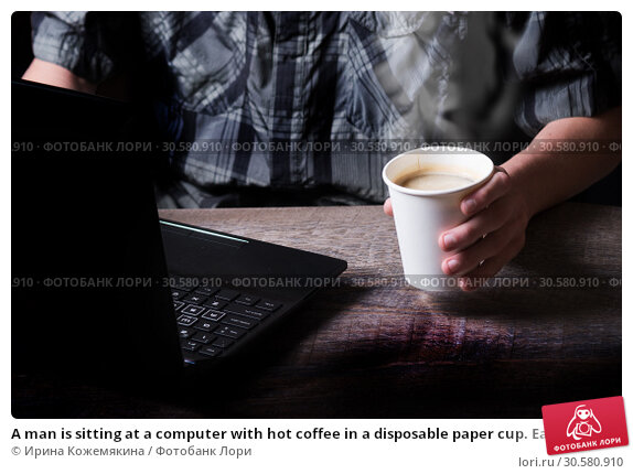 Купить «A man is sitting at a computer with hot coffee in a disposable paper cup. Early morning», фото № 30580910, снято 28 марта 2019 г. (c) Ирина Кожемякина / Фотобанк Лори