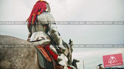 Купить «A man knight in helmet with fabric clippings riding a horse on the battlefield», видеоролик № 32020306, снято 17 августа 2019 г. (c) Константин Шишкин / Фотобанк Лори