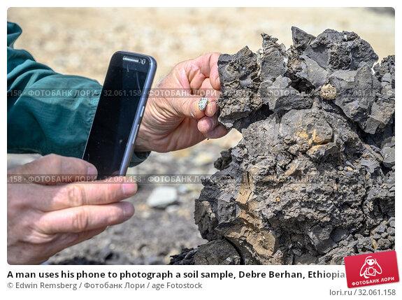 A man uses his phone to photograph a soil sample, Debre Berhan, Ethiopia. Стоковое фото, фотограф Edwin Remsberg / age Fotostock / Фотобанк Лори