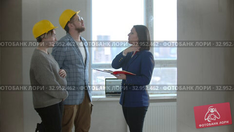 A pregnant woman with her husband talking with a real estate agent in apartment in a new building. Стоковое видео, видеограф Константин Шишкин / Фотобанк Лори