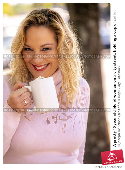 A pretty 40 year old blond woman on a city street, holding a cup of coffee and looking at the camera. Стоковое фото, фотограф Joseph De Sciose / age Fotostock / Фотобанк Лори