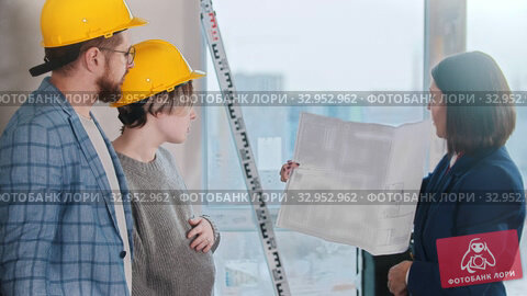 A real estate agent showing a layout to a young married couple - discussing the plan. Стоковое видео, видеограф Константин Шишкин / Фотобанк Лори