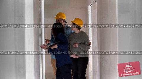 A real estate agent showing a new draft apartment to a family. Стоковое видео, видеограф Константин Шишкин / Фотобанк Лори
