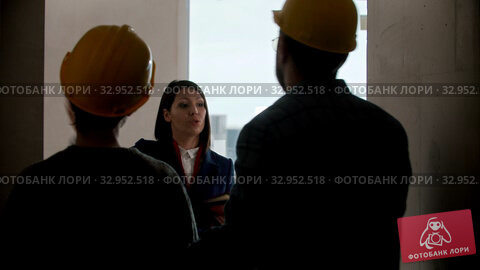 A real estate agent showing a new draft apartment to a family - pointing at the walls and talking. Стоковое видео, видеограф Константин Шишкин / Фотобанк Лори