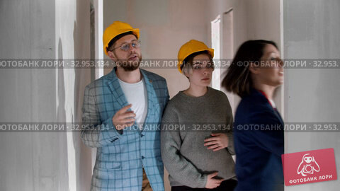 A real estate agent showing a new draft apartment to a young married couple in helmets - looking around. Стоковое видео, видеограф Константин Шишкин / Фотобанк Лори