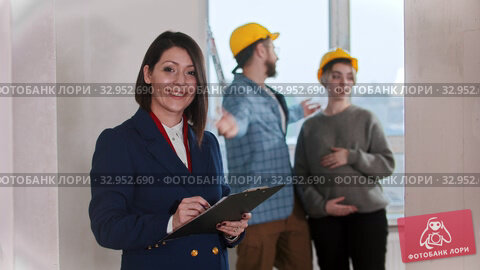 A real estate agent signing papers and smiling in draft apartment - young married couple looking around on the background. Стоковое видео, видеограф Константин Шишкин / Фотобанк Лори