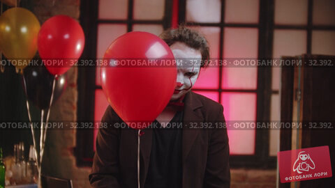 Купить «A scary clown peeking out from the red balloon and creepy smiling», видеоролик № 32392138, снято 14 ноября 2019 г. (c) Константин Шишкин / Фотобанк Лори