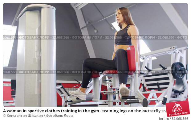 A woman in sportive clothes training in the gym - training legs on the butterfly training apparatus. Стоковое фото, фотограф Константин Шишкин / Фотобанк Лори