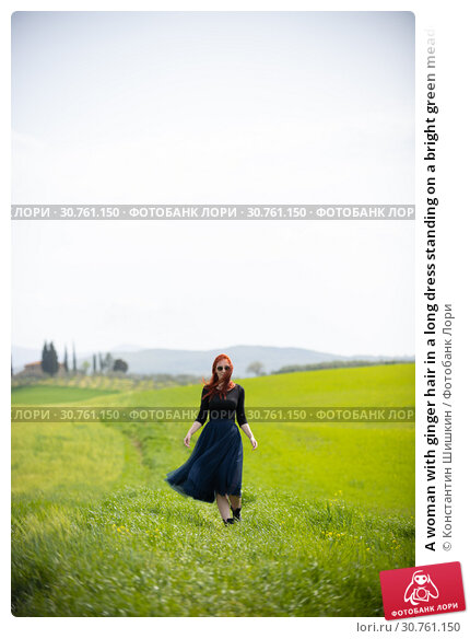 Купить «A woman with ginger hair in a long dress standing on a bright green meadow», фото № 30761150, снято 24 апреля 2019 г. (c) Константин Шишкин / Фотобанк Лори