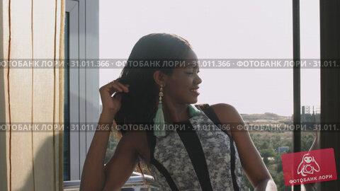Купить «A young African-American woman with dark hair in a dress is standing on the balcony and smiling», видеоролик № 31011366, снято 4 августа 2020 г. (c) Denis Mishchenko / Фотобанк Лори
