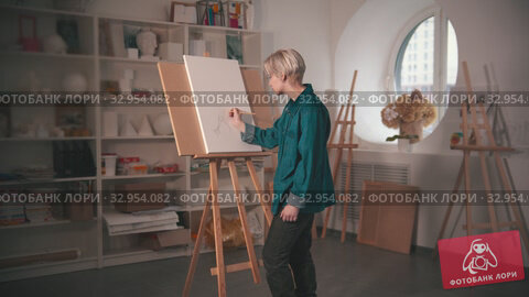 A young blonde woman artist drawing sketch on the canvas and looking at it. Стоковое видео, видеограф Константин Шишкин / Фотобанк Лори