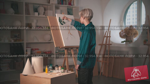 A young blonde woman artist painting upper branches of tree in green color in the art studio. Стоковое видео, видеограф Константин Шишкин / Фотобанк Лори