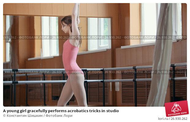 Купить «A young girl gracefully performs acrobatics tricks in studio», фото № 26930262, снято 24 мая 2018 г. (c) Константин Шишкин / Фотобанк Лори
