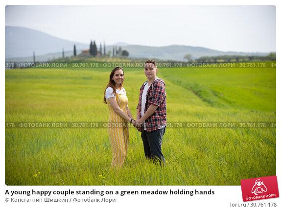 Купить «A young happy couple standing on a green meadow holding hands», фото № 30761178, снято 24 апреля 2019 г. (c) Константин Шишкин / Фотобанк Лори