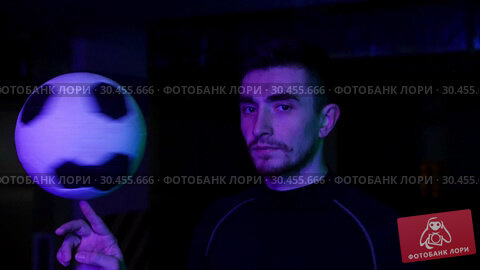 A young man on the underground parking throws the ball up and spinning it on his finger in neon lighting. Turns his look in the camera. Стоковое видео, видеограф Константин Шишкин / Фотобанк Лори