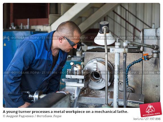 A young turner processes a metal workpiece on a mechanical lathe. (2017 год). Редакционное фото, фотограф Андрей Радченко / Фотобанк Лори