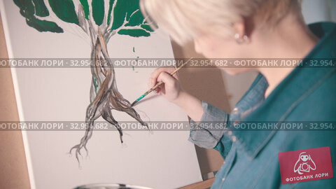 Купить «A young woman with short hair painting tree trunk in darker color», видеоролик № 32954682, снято 27 мая 2020 г. (c) Константин Шишкин / Фотобанк Лори