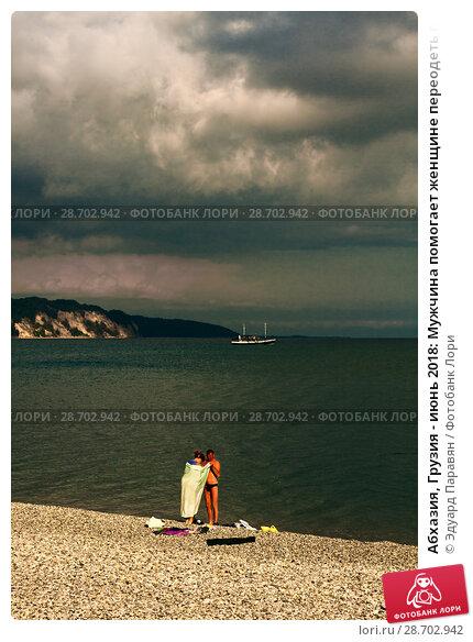 Купить «Абхазия, Грузия - июнь 2018: Мужчина помогает женщине переодеть плавки  на галечном пляже Лдзаа в Пицунде», фото № 28702942, снято 8 июня 2018 г. (c) Эдуард Паравян / Фотобанк Лори