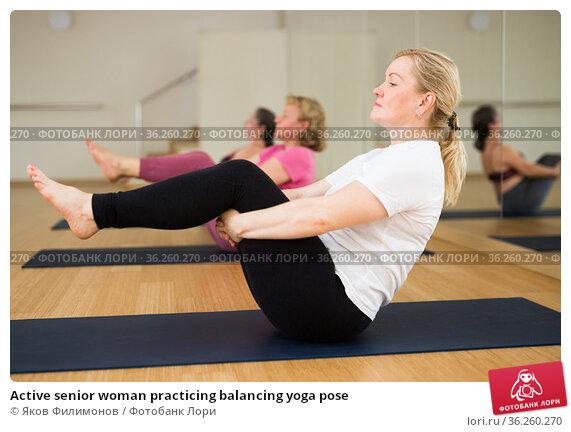 Active senior woman practicing balancing yoga pose. Стоковое фото, фотограф Яков Филимонов / Фотобанк Лори