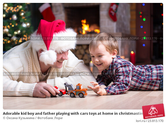Купить «Adorable kid boy and father playing with cars toys at home in christmastime. Happy child having fun with gifts. Colorful christmas lights on background. Family and holiday lifestyle concept.», фото № 23813170, снято 16 января 2016 г. (c) Оксана Кузьмина / Фотобанк Лори