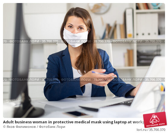 Adult business woman in protective medical mask using laptop at workplace. Стоковое фото, фотограф Яков Филимонов / Фотобанк Лори