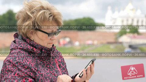 Купить «Adult woman tourist holding a smartphone outdoors», видеоролик № 26603830, снято 30 июня 2017 г. (c) worker / Фотобанк Лори
