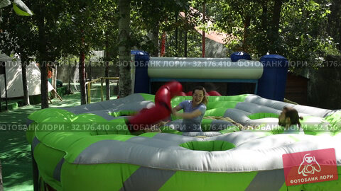 Adults having fun on inflatable playground. Cheerful young woman fighting off her friends with inflatable beam while they hunting for her toy chickens. Стоковое видео, видеограф Яков Филимонов / Фотобанк Лори