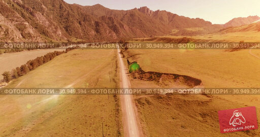 Купить «Aerial rural mountain road and meadow at sunny summer morning. Asphalt highway and river.», видеоролик № 30949394, снято 2 декабря 2017 г. (c) Александр Маркин / Фотобанк Лори
