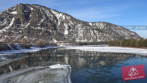 Купить «Aerial view on Altai river Katun with floating of ice in water and mountains on background in winter season», видеоролик № 25669594, снято 27 февраля 2017 г. (c) Serg Zastavkin / Фотобанк Лори