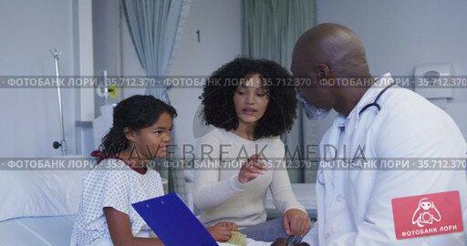 African american senior male doctor with clipboard talking to mother and daughter at hospital. Стоковое видео, агентство Wavebreak Media / Фотобанк Лори